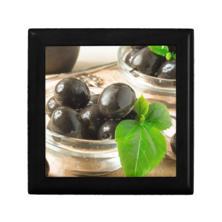 Brown pickled olives on the old wooden background gift box