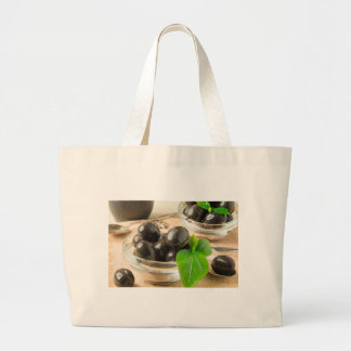 Brown pickled olives on the old wooden background large tote bag