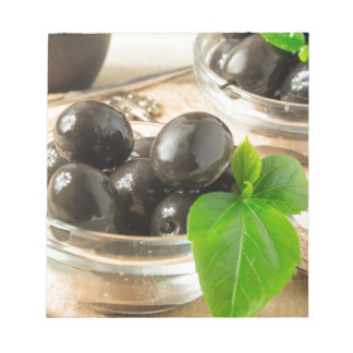 Brown pickled olives on the old wooden background notepad