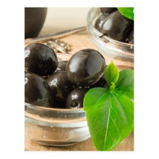 Brown pickled olives on the old wooden background postcard