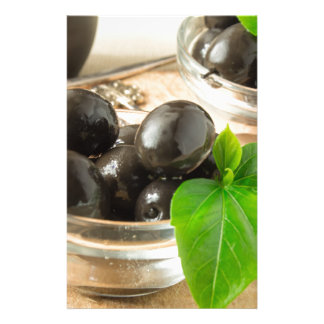 Brown pickled olives on the old wooden background stationery