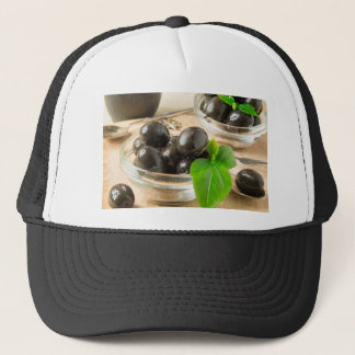 Brown pickled olives on the old wooden background trucker hat
