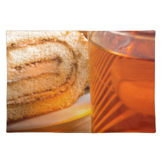 Brown sponge cake and cup of hot tea placemat