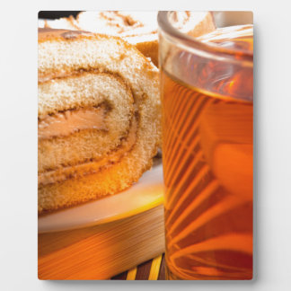 Brown sponge cake and cup of hot tea plaque