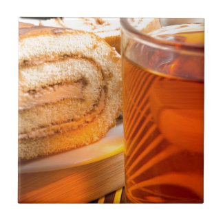 Brown sponge cake and cup of hot tea tile