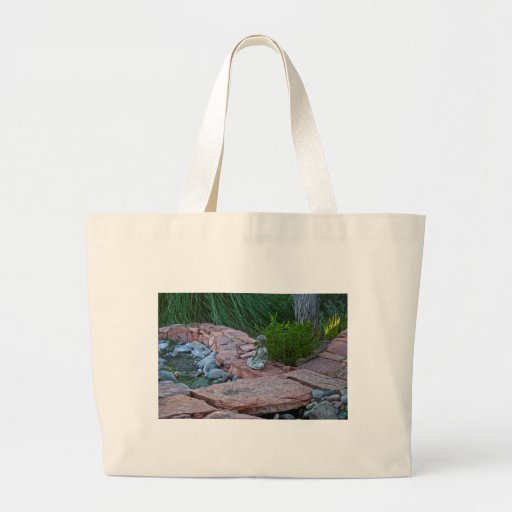 Buda meditating by the stream canvas bags