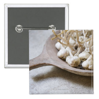 Bulbs of garlic in an earthenware bowl 2 inch square button