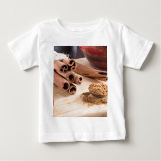 Bunch of cinnamon sticks and vintage silver spoon baby T-Shirt