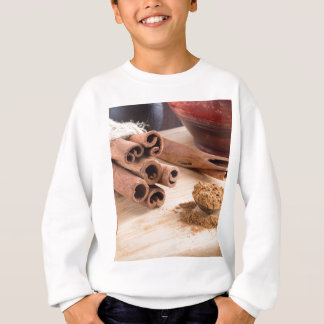 Bunch of cinnamon sticks and vintage silver spoon sweatshirt