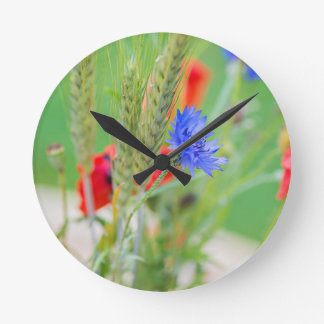 Bunch of of red poppies, cornflowers and ears round clock