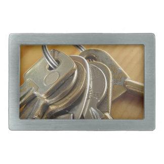 Bunch of worn house keys on wooden table belt buckle