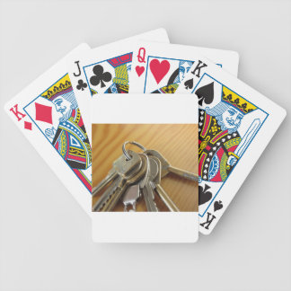 Bunch of worn house keys on wooden table bicycle playing cards