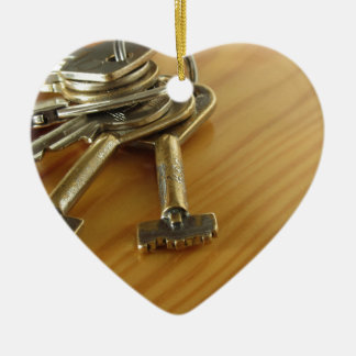 Bunch of worn house keys on wooden table ceramic heart ornament