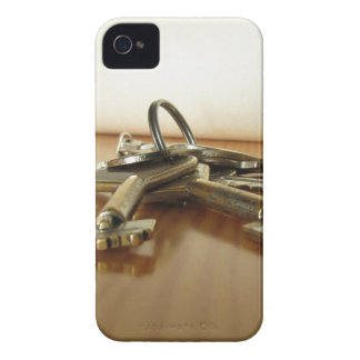 Bunch of worn house keys on wooden table iPhone 4 case