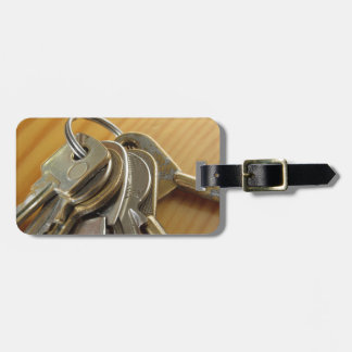 Bunch of worn house keys on wooden table luggage tag