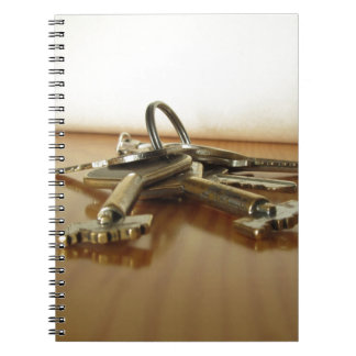 Bunch of worn house keys on wooden table notebook