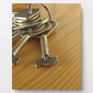 Bunch of worn house keys on wooden table plaque