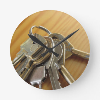 Bunch of worn house keys on wooden table round clock