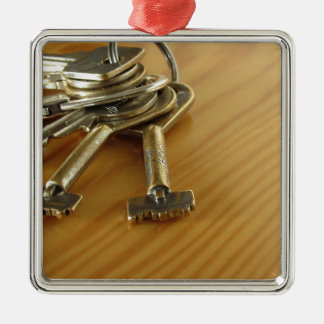 Bunch of worn house keys on wooden table Silver-Colored square ornament