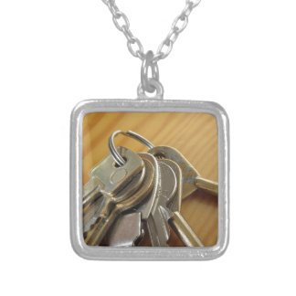 Bunch of worn house keys on wooden table silver plated necklace