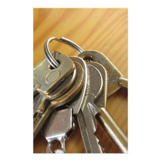 Bunch of worn house keys on wooden table stationery