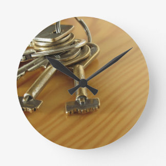Bunch of worn house keys on wooden table wall clock