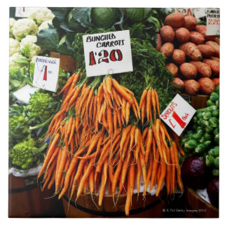 Bunches of carrots and vegetables on market tile