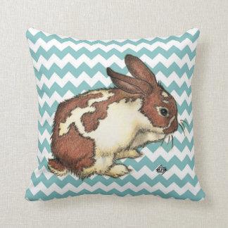 Bunny washing his face with blue chevron throw pillows