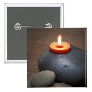 Burning candle flame with rocks in tranquil pins