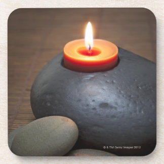 Burning candle flame with rocks in tranquil coaster