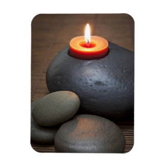 Burning candle flame with rocks in tranquil rectangular magnet