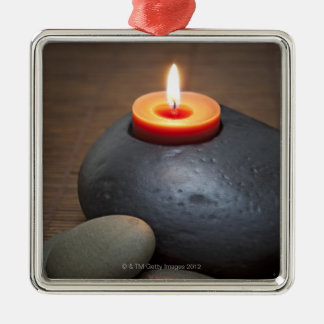 Burning candle flame with rocks in tranquil Silver-Colored square ornament