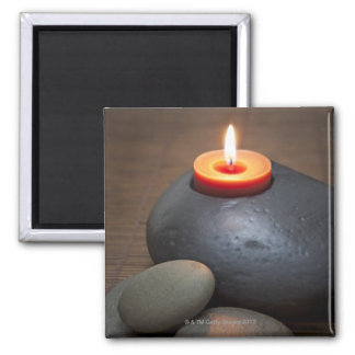 Burning candle flame with rocks in tranquil square magnet