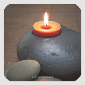 Burning candle flame with rocks in tranquil square sticker