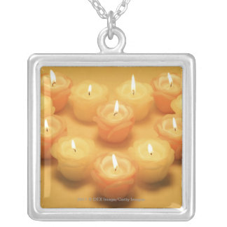 Burning candles arranged in a heart shape silver plated necklace