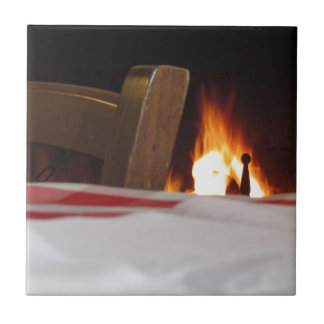 Burning fireplace and old vintage chair ceramic tile