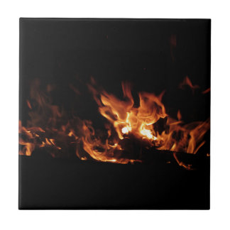 Burning fireplace with fire flames on black ceramic tile