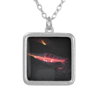 Burning fireplace with fire flames on black silver plated necklace