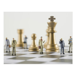 Businessmen figurines standing a top chess board postcard
