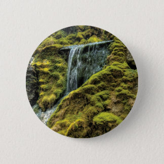 By a small waterfall 2 inch round button