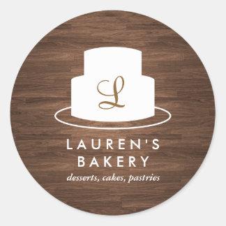 Cake Monogram Logo in White on Brown Woodgrain Round Sticker