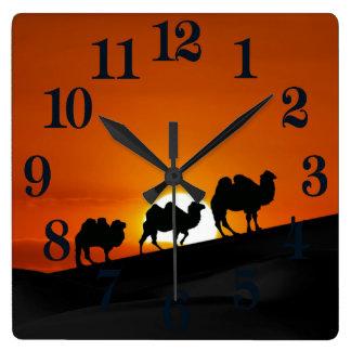 Camels at sunset square wall clock