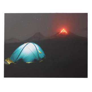 Camping at night on background of active volcano notepad