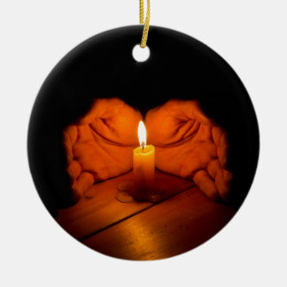 Candle, hands, flame, wood. round ceramic ornament