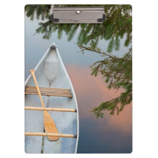 Canoe on lake at sunset, Canada Clipboards