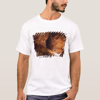 Canyoneer illuminated in the depths of a narrow T-Shirt