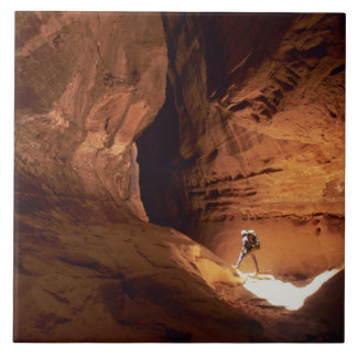Canyoneer illuminated in the depths of a narrow tile