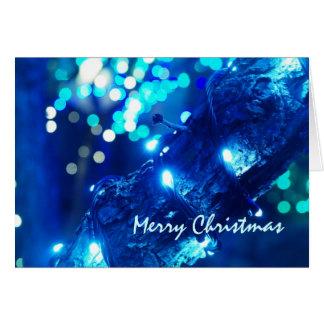Carte de voeux bleue de lumières de Noël
