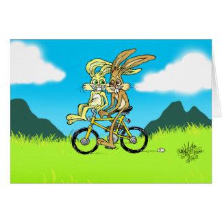 Cartoon bunnies on a bicycle. on a greeting card. card