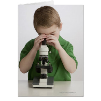 Caucasian boy peering into microscope card